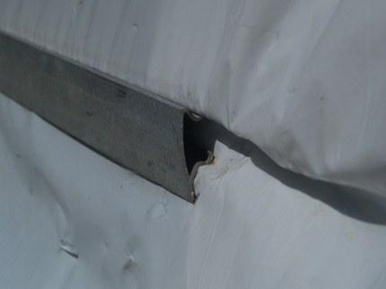 Metal fasteners holding plastic to bandboard, hipboard, or endwal
