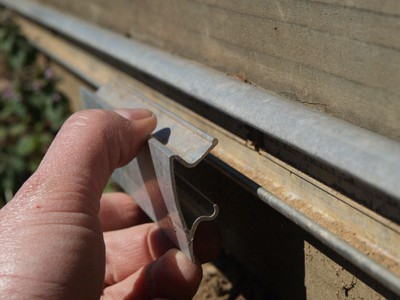 Metal fasteners for holding plastic to bandboard, hipboard, or endwall