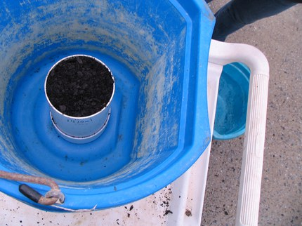 Water from pore spaces drains into bucket
